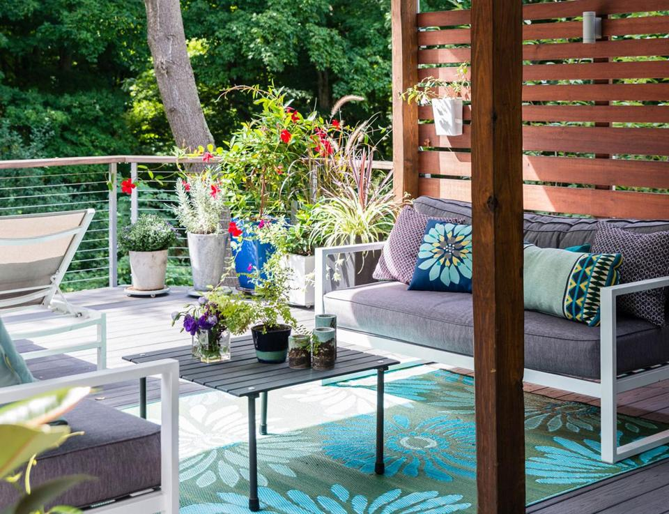 With a waterproof ceiling, ceiling fans, indoor-outdoor rug, and facing sofas, the lower-level deck functions as an outdoor room. Privacy screens shield the space.